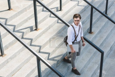 high angle view of handsome young man walking on stairs with laptop on city street