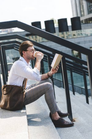handsome young man drinking coffee from paper cup and reading book on stairs on city street
