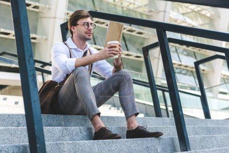 Photo pour Jeune homme élégant gobelet en papier du livre de lecture du café dans les escaliers sur la rue de la ville - image libre de droit