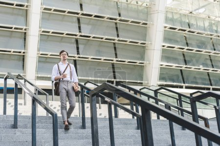 handsome young man walking down stairs in front of stadium with book and coffee to go