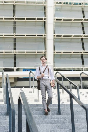 stylish young man walking down stairs in front of stadium with book and coffee to go