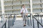 """Постер, картина, фотообои """"привлекательный молодой человек ходить вниз лестнице перед стадион с книгой и кофе идти"""""""
