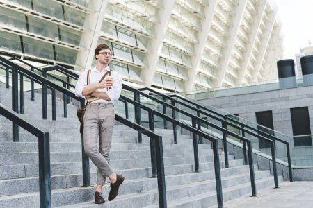 attractive young man standing on stairs in front of stadium with book and coffee to go