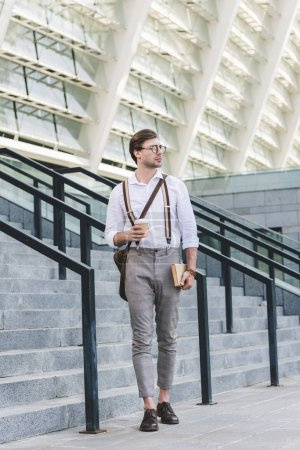 attractive young man walking in front of stadium with book and coffee to go