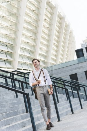 stylish young man walking in front of stadium with book and coffee to go