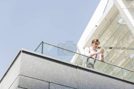 bottom view of attractive young man using smartphone on balcony