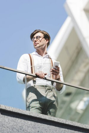 bottom view of stylish young man using smartphone on balcony