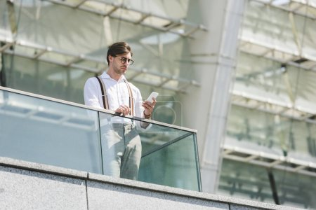 bottom view of handsome young man using smartphone on balcony in front of stadium