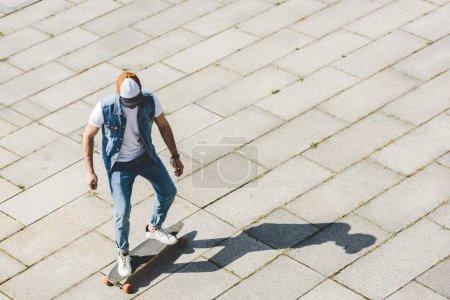 Photo pour Vue grand angle de jeune patineur élégant chevauchant longboard par carré - image libre de droit