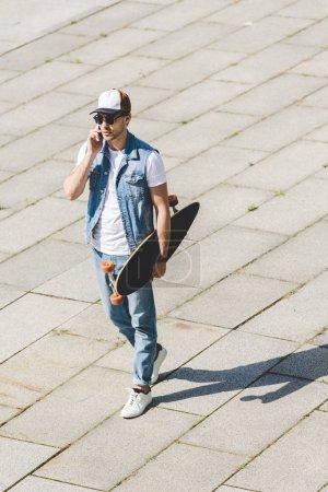 Photo pour Vue grand angle de beau jeune skateboarder marchant avec longboard à la main et parlant par téléphone - image libre de droit