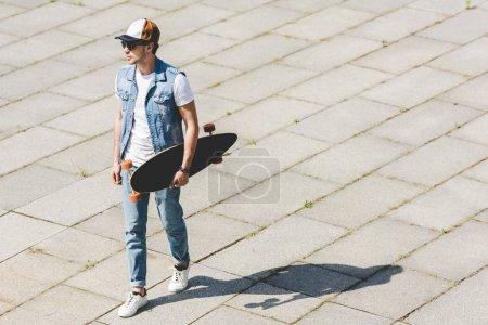 Photo pour Vue grand angle de beau jeune homme marchant avec planche à roulettes à la main - image libre de droit