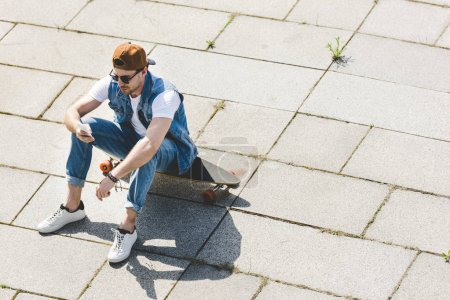 high angle view of stylish young man sitting on skateboard and using smartphone