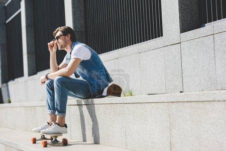 Photo pour Séduisant jeune homme assis dans les escaliers avec la planche à roulettes à la recherche. - image libre de droit