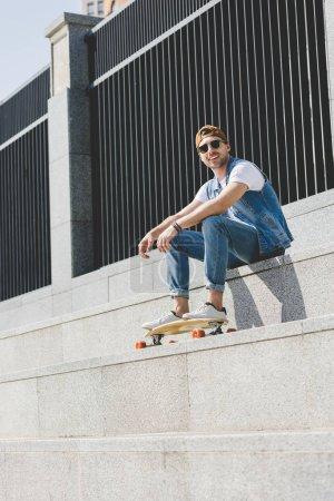 Photo pour Vue de dessous du beau jeune patineur assis dans les escaliers avec longboard - image libre de droit