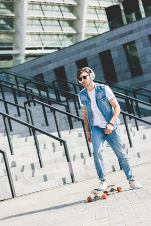 handsome young skater in headphones riding longboard in front of stadium