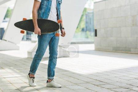 Photo pour Recadrée tir du patineur dans les vêtements de denim avec planche à roulettes - image libre de droit