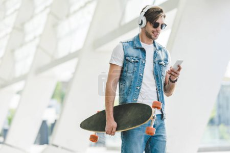 Handsome young man with longboard using smartphone...