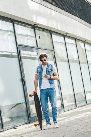 Photo pour Beau jeune skateur avec longboard à l'aide de smartphone - image libre de droit