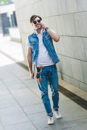 Photo pour Sourire de jeune homme avec skateboard parler par téléphone - image libre de droit