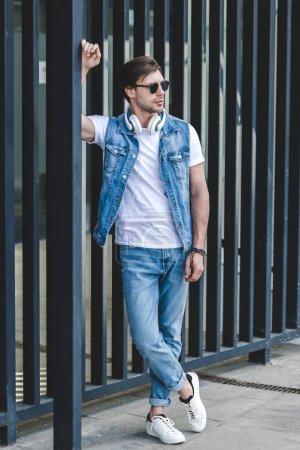 Photo pour Beau jeune homme en gilet en denim appuyé sur la clôture sur la rue de la ville - image libre de droit