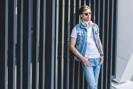 Photo pour Beau jeune homme en penchant de veste de denim de retour sur la clôture sur la rue de la ville - image libre de droit
