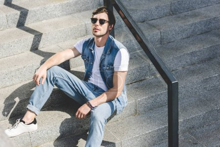 handsome young man sitting on stairs and relaxing