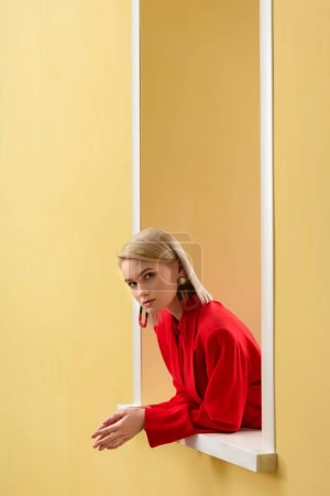 side view of blond stylish woman in red suit looking out decorative window