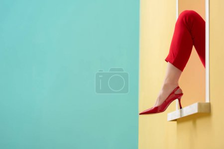 cropped shot of female leg in red shoe outstretched out decorative window