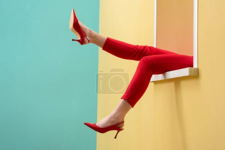 Photo for Partial view of woman in red pants and shoes outstretching legs out decorative window - Royalty Free Image