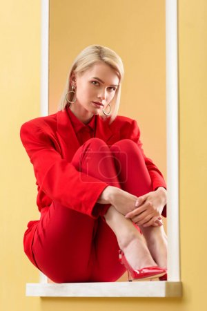 beautiful blond woman in stylish red suit sitting on decorative window