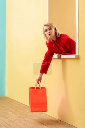 young fashionable woman in red clothing with red shopping bags looking out decorative window