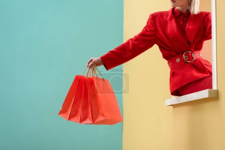 Photo for Cropped shot of fashionable woman in red clothing with red shopping bags sitting on decorative window - Royalty Free Image
