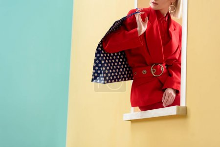 cropped shot of stylish woman with shopping bag with dots pattern sitting on decorative window