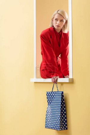 stylish pensive woman in red suit with shopping bag with dots pattern in hand sitting on decorative window