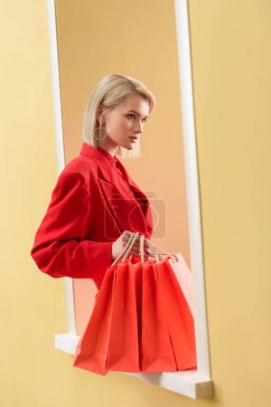 young fashionable woman in red clothing with red shopping bags sitting on decorative window