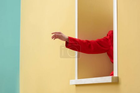 cropped shot of woman in red jacket sticking hand out decorative window