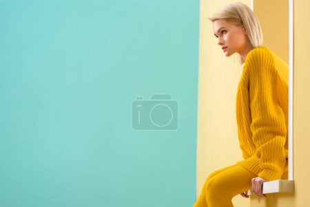 Photo for Side view of stylish woman in yellow sweater and tights sitting on decorative window - Royalty Free Image