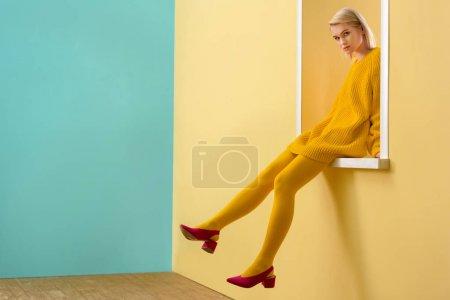 Photo pour Vue latérale de la femme élégante en chaussures roses, pull jaune et collants assis sur la fenêtre décorative - image libre de droit