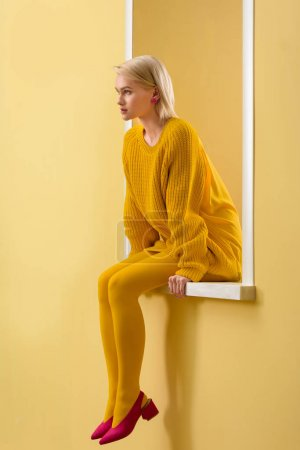 Photo for Side view of stylish woman in pink shoes, yellow sweater and tights sitting on decorative window - Royalty Free Image
