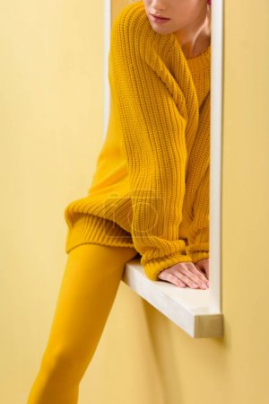 cropped shot of stylish woman in yellow sweater and tights sitting on decorative window