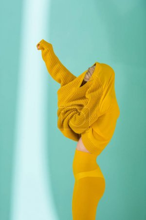 side view of woman in yellow tights wearing yellow sweater posing on blue background