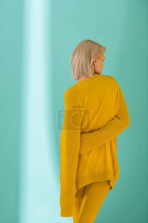 back view of woman in yellow sweater posing on blue background