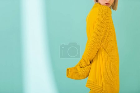 partial view of woman in yellow sweater posing on blue background