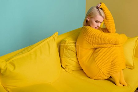side view of young blond woman in yellow sweater and tights sitting on yellow sofa on blue backdrop