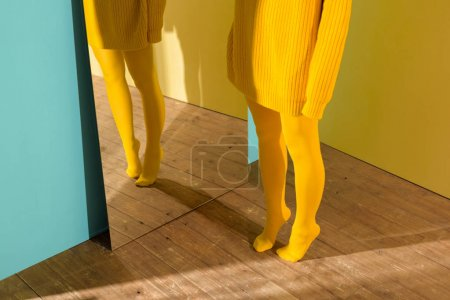 cropped shot of woman in yellow sweater and tights standing at mirror