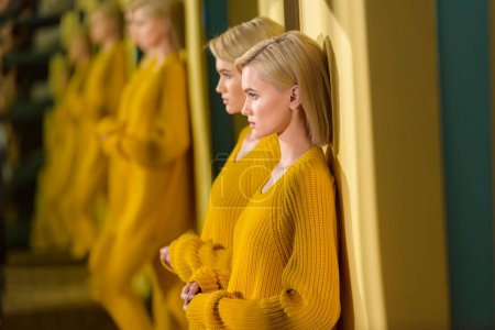 selective focus of blond woman in yellow sweater and tights standing at mirror with her reflection in it