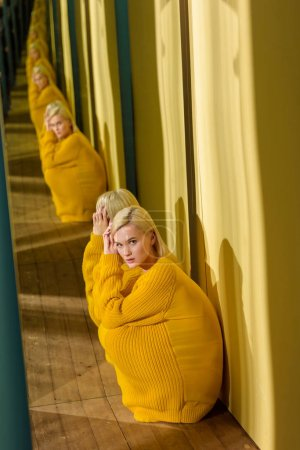 side view of beautiful young woman in yellow sweater sitting at mirror with her reflection in it