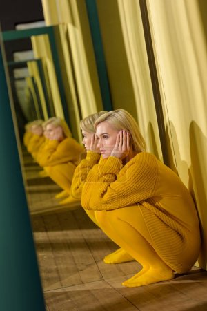 side view of beautiful thoughtful woman in yellow sweater sitting at mirror with her reflection in it