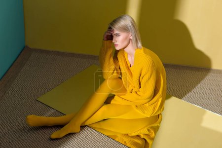 high angle view of beautiful young woman in yellow sweater and tights sitting on mirror with reflection in it