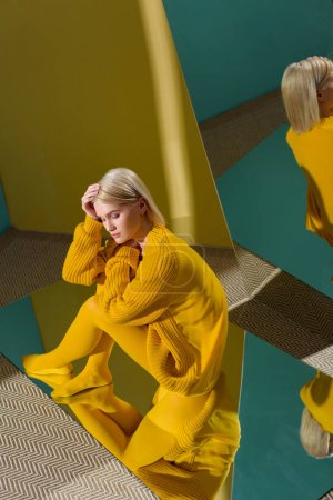 high angle view of attractive woman in yellow sweater and tights sitting on mirror with reflection in it